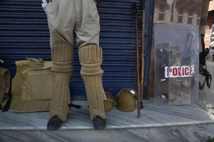 FILE - In this Thursday, Aug. 22, 2019 file photo, a Kashmiri policeman guards outside a closed shop in Srinagar, Indian-controlled Kashmir. Police in Indian-controlled Kashmir said Friday, April 16, 2021, that they arrested one of their own officers and dismissed her for obstructing a counterinsurgency operation in the disputed region. Indian law enforcement officers repeatedly have been implicated in helping Kashmiri rebels, who for decades have waged an armed campaign demanding independence for their Himalayan region or a merger with neighboring Pakistan, which administers a part of Kashmir. (AP Photo/Mukhtar Khan, File)