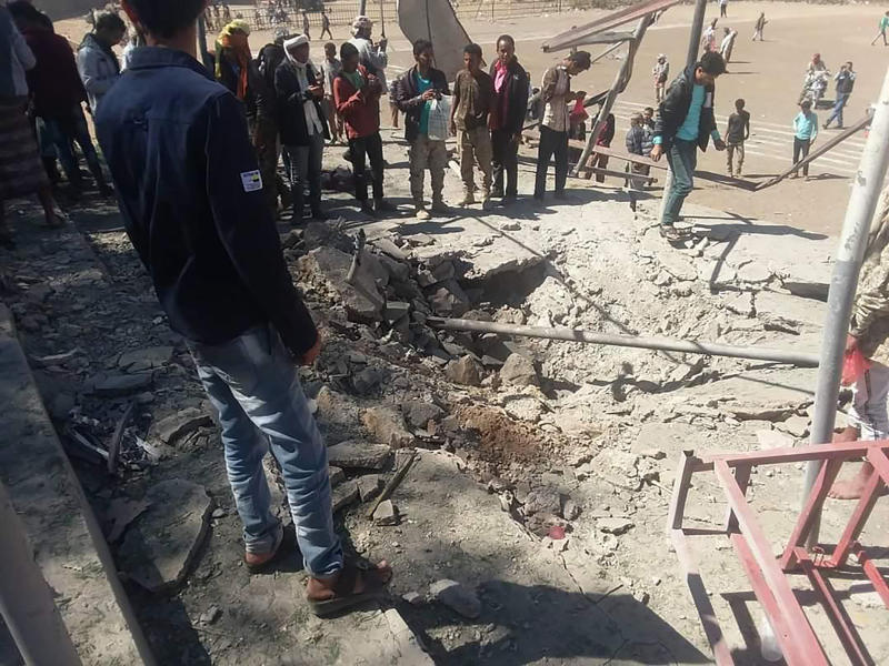 In this photo provided by southern separatist forces in Yemen, known as Resistance Force, a crowd of people stand around a crater created by a missile attack on a military parade in Dhale, Yemen Sunday, Dec. 29, 2019. A ballistic missile attack ripped through a military parade for the Yemeni southern separatist group that's backed by the United Arab Emirates,  a spokesman said Sunday. (Resistance Forces via AP)