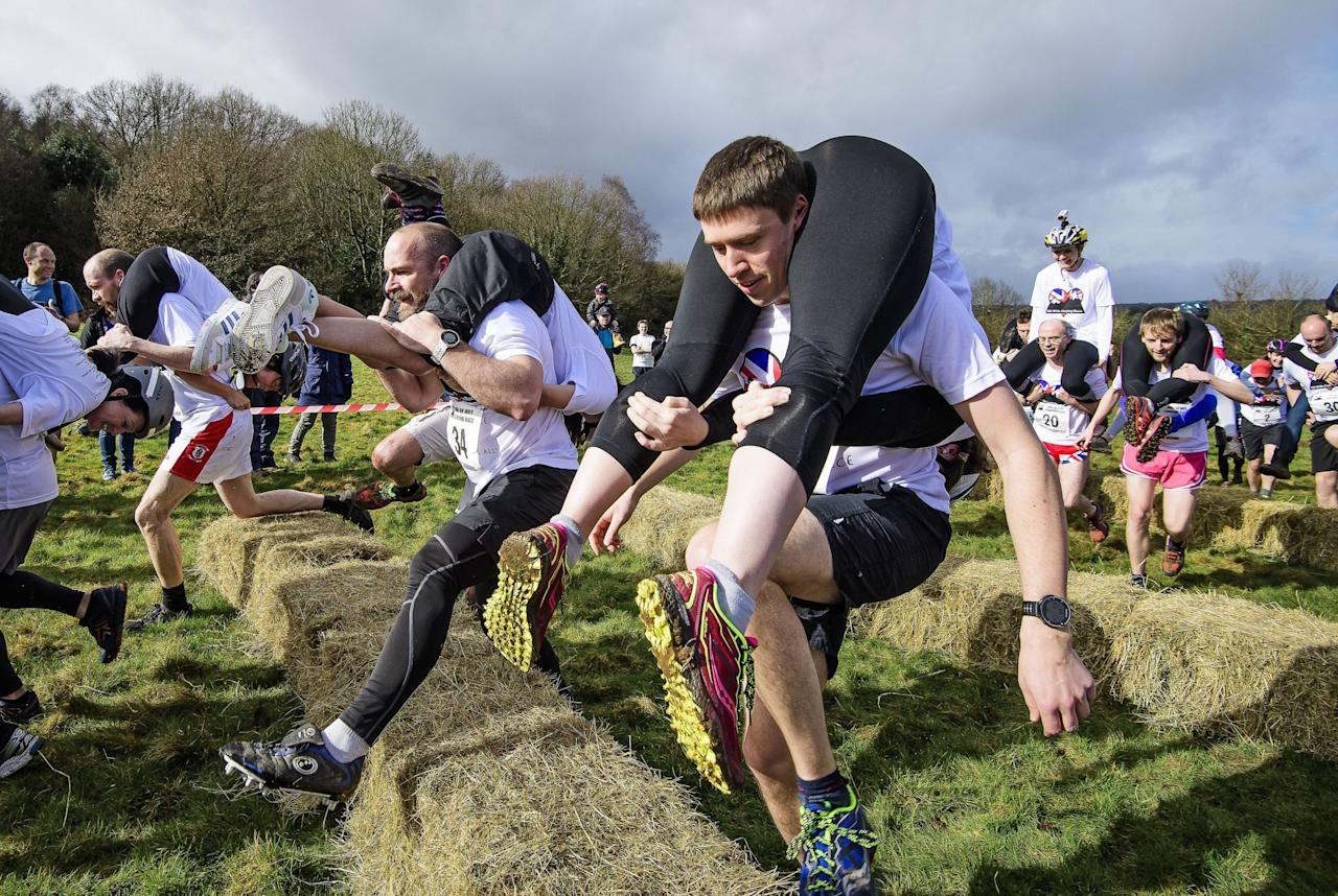 <p>Competitors take part in the 2017 Wife Carrying Race in Dorking, Surrey. (Rex) </p>