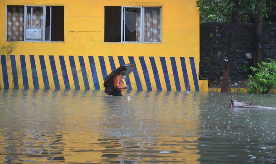 A man wades through a flooded road in Mumbai. (Photo by Arun Patil)