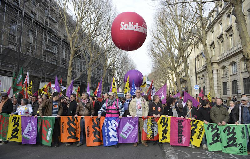 """French CGT and FO union members demonstrate to protest the Socialist government's plans to loosen this country's famously rigid labor rules, Paris, Tuesday, March 5, 2013. Multinationals are shutting factories around France amid Europe's economic slowdown. France's government is trying to stem job losses and turn the stagnant economy around with a new draft labor law being presented at a Cabinet meeting Wednesday. Writing on balloon reads, """"Solidarity"""". (AP Photo/Benjamin Girette)"""