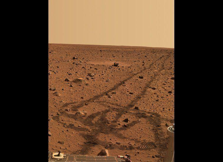 "While driving over the reddish rocks and soils of Mars, the rover's wheels dig below the thin dusty layer and reveal darker, brownish soils just below. The circular tracks are ""pirouettes"" that the rovers occasionally do to align their radio antennas for best possible communications. <em>Spirit rover, Pancam image, mission sol (martian day) 141 (May 26, 2004). From ""Postcards from Mars"" by Jim Bell; Photo credit: NASA/JPL/Cornell University</em>"