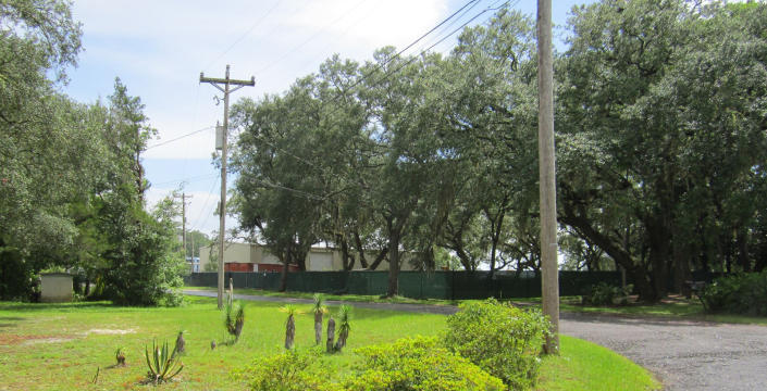Picture from the road, through telephone poles, trees and fencing, of the maritime company that officially employed Stanek and the other crew members.
