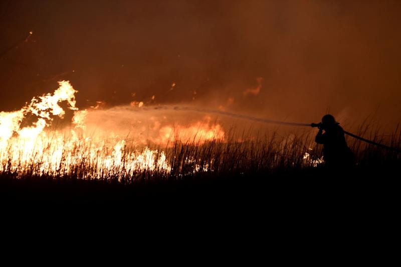 A firefighter works to control the Rheawildfire near Seiling, Oklahoma,on April 17.