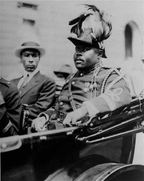"""FILE - In this Aug. 1922 file photo, Marcus Garvey is shown in a military uniform as the """"Provisional President of Africa"""" during a parade on the opening day of the annual Convention of the Negro Peoples of the World at Lenox Avenue in Harlem, New York City. A century ago, Garvey helped spark movements from African nationalist independence to American civil rights to self-sufficiency in black commerce. Jamaican students in every grade from kindergarten through high school have began studying the teachings of the 1920-era black nationalist leader in a new mandatory civics program in schools across this predominantly black country of 2.8 million people. (AP Photo/File)"""