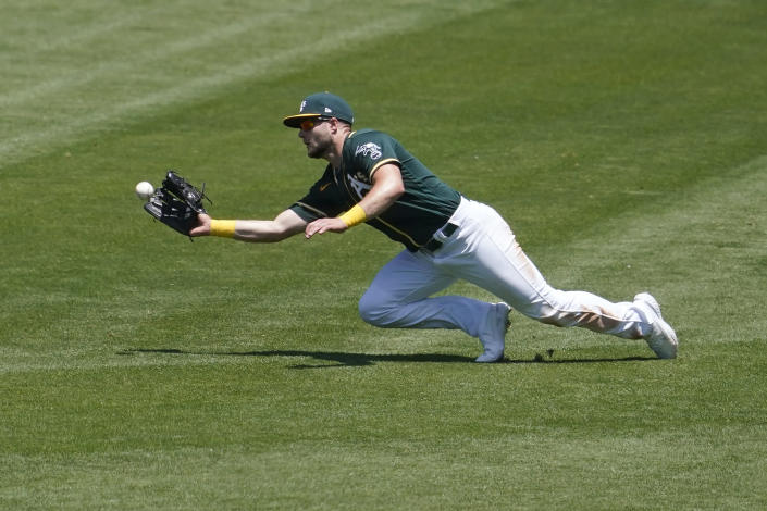 Oakland Athletics right fielder Seth Brown catches a line out hit by Texas Rangers' Andy Ibanez during the third inning of a baseball game in Oakland, Calif., Thursday, July 1, 2021. (AP Photo/Jeff Chiu)