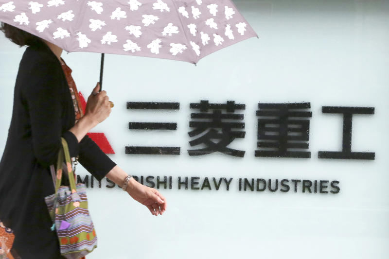 A woman walks past the company sign of the Mitsubishi Heavy Industries in Tokyo Tuesday, July 16, 2019. Colonial-era Korean laborers are seeking a court approval for the sales of local assets of their former Japanese company as it is refusing to compensate them. Lawyers for Koreans who worked for the Japanese company say they'll soon request a South Korean court to authorize the sales of some of Mitsubishi's seized assets in South Korea. (AP Photo/Koji Sasahara)