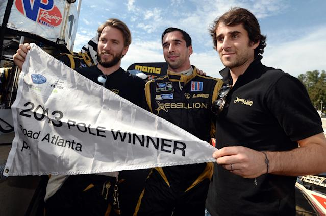 From left, Nick Heidfeld, of Germany, Neel Jani, of Switzerland, and Nicolas Prost, of France, celebrate their P1 class pole position after qualifying for the American Le Mans Series' Petit Le Mans auto race at Road Atlanta, Friday, Oct. 18, 2013, in Braselton, Ga. (AP Photo/Rainier Ehrhardt)