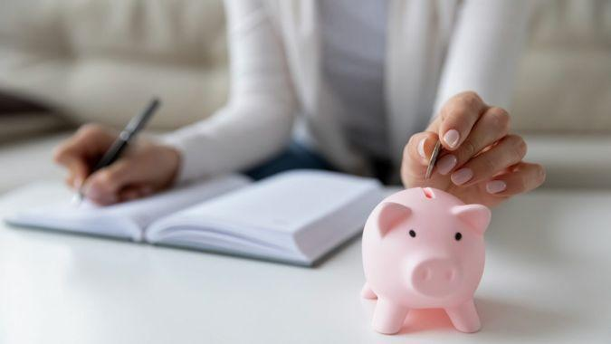 Thrifty woman sit at table hold pen writing daily expenses in diary put coin in pink piggy bank close up.