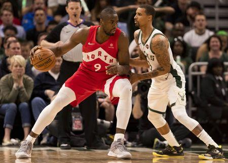 May 23, 2019; Milwaukee, WI, USA; Toronto Raptors center Serge Ibaka (9) dribbles the ball as Milwaukee Bucks guard George Hill (3) defends during the third quarter in game five of the Eastern conference finals of the 2019 NBA Playoffs at Fiserv Forum. Mandatory Credit: Jeff Hanisch-USA TODAY Sports