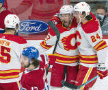 Calgary Flames Josh Leivo (27) celebrates with teammates Brett Ritchie (24) and Noah Hanifin (55) after scoring the third goal as Montreal Canadiens' Josh Anderson (17) skates by during the third period of an NHL hockey game Wednesday, April 14, 2021 in Montreal. (Ryan Remiorz/Canadian Press via AP)