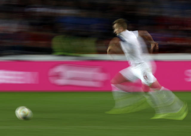 FILE - In this Oct. 11, 2019, file image taken with a slow shutter speed a soccer player runs for the ball during the Euro 2020 group A qualifying soccer match in Prague, Czech Republic. A study, from the University of Glasgow and reported Monday, Oct. 21, in New England Journal of Medicine, of former professional soccer players in Scotland found that they were less likely to die of common causes such as heart disease and cancer compared with the general population but more likely to die from dementia. (AP Photo/Petr David Josek, File)