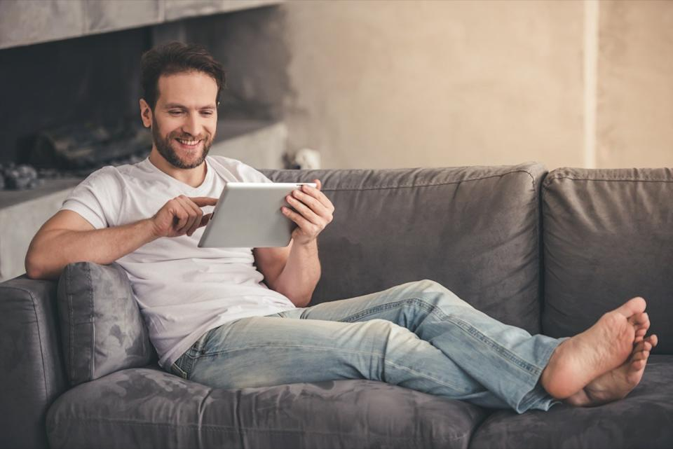 Handsome man is using a digital tablet and smiling while resting on couch at home