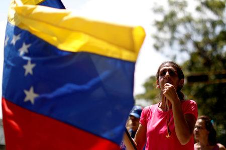 A woman whistles as she and others block a street to show their anger because of the ongoing blackout in Caracas