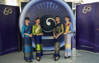 Flight attendants pose for a photo in a flight-themed restaurant at the Thai Airways head office in Bangkok, Thailand on Oct. 3, 2020. The airline is selling time on its flight simulators to wannabe pilots while its catering division is serving meals in a flight-themed restaurant complete with airline seats and attentive cabin crew. The airline is trying to boost staff morale, polish its image and bring in a few pennies, even as it juggles preparing to resume international flights while devising a business reorganization plan. (AP Photo/Sakchai Lalit)