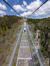 A woman walks across a narrow footbridge suspended across a river canyon, which claims to be the world's longest pedestrian bridge, in Arouca, northern Portugal, Sunday, May 2, 2021. The Arouca Bridge inaugurated Sunday, offers a half-kilometer (almost 1,700-foot) walk across its span, some 175 meters (574 feet) above the River Paiva. (AP Photo/Sergio Azenha)