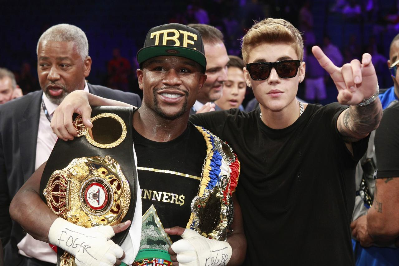 Floyd Mayweather Jr. (L) and singer Justin Bieber celebrate Mayweather's victory over WBC/WBA 154-pound champion Canelo Alvarez (not pictured) at the MGM Grand Garden Arena in Las Vegas, Nevada, September 14, 2013. Alvarez was previously undefeated in 42 fights. REUTERS/Steve Marcus (UNITED STATES - Tags: SPORT BOXING ENTERTAINMENT)