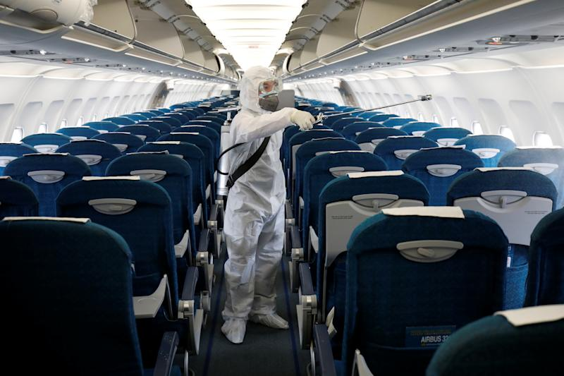 A health worker sprays disinfectant inside a Vietnam Airlines airplane to protect from the recent coronavirus outbreak, at Noi Bai airport in Hanoi, Vietnam February 21, 2020. REUTERS/Kham