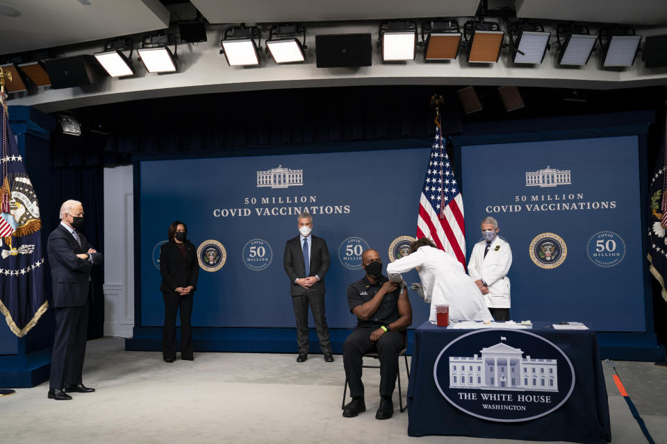 President Joe Biden looks on as Washington DC firefighter and EMT Gerald Burn receives a vaccination, during an event to commemorate the 50 millionth COVID-19 shot, in the South Court Auditorium on the White House campus, Thursday, Feb. 25, 2021, in Washington. From left, Biden, Vice President Kamala Harris, White House COVID-19 Response Coordinator Jeff Zients, Burn, registered nurse Elizabeth Galloway, and director of the National Institute of Allergy and Infectious Diseases Dr. Anthony Fauci. (AP Photo/Evan Vucci)