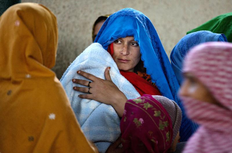 In this Thursday, Dec. 12, 2103 photo, a Pakistani woman waits with others to receive free food in Islamabad, Pakistan. Non-governmental organizations in Pakistan estimate the country has the highest rate of breast cancer in Asia. An estimated one in nine women will risk breast cancer during their life, according to PinkRibbon, an international group working on campaigns against the disease. (AP Photo/Fareed Khan)