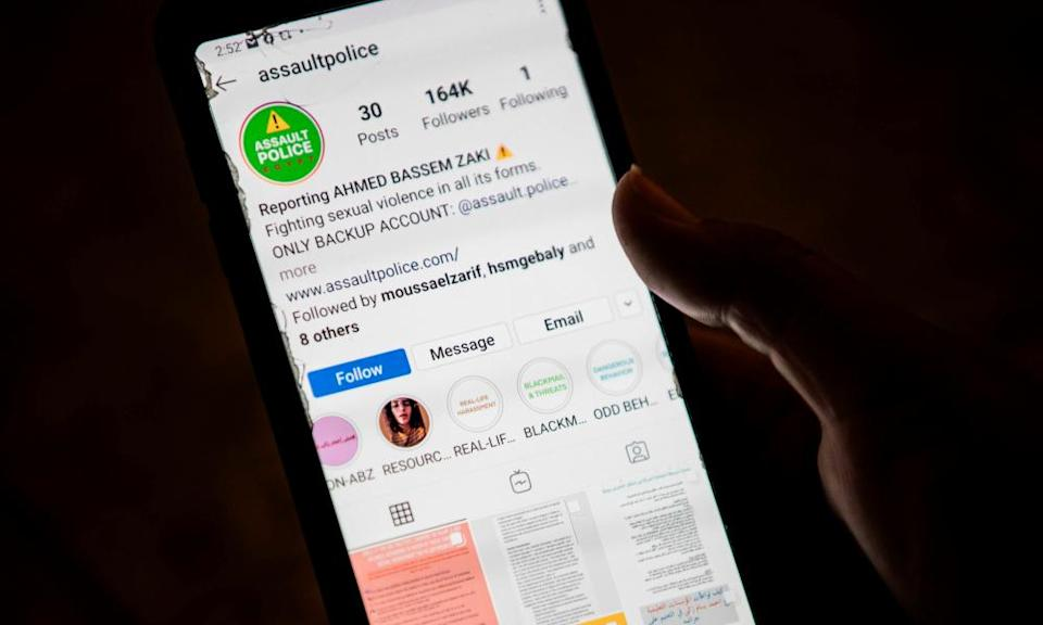 A woman checks on her phone an Instagram account for reporting allegations against Ahmed Bassam Zaki