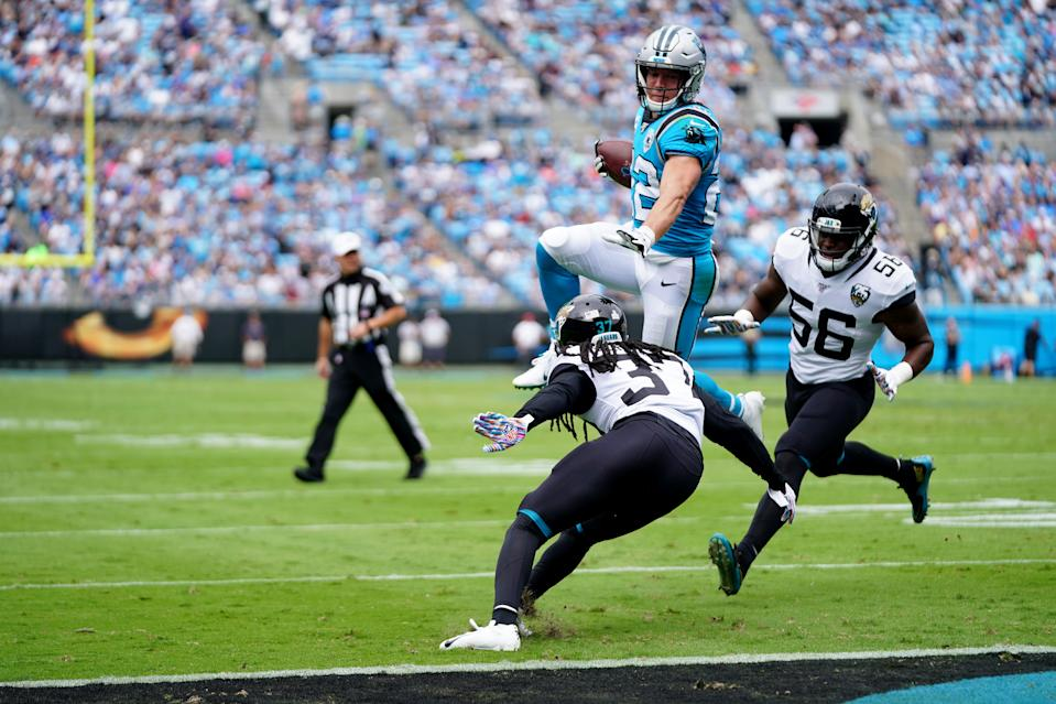CHARLOTTE, NORTH CAROLINA - OCTOBER 06: Christian McCaffrey #22 of the Carolina Panthers scores a touchdown by leaping over Tre Herndon #37 of the Jacksonville Jaguars in the first quarter during their game at Bank of America Stadium on October 06, 2019 in Charlotte, North Carolina. (Photo by Jacob Kupferman/Getty Images)