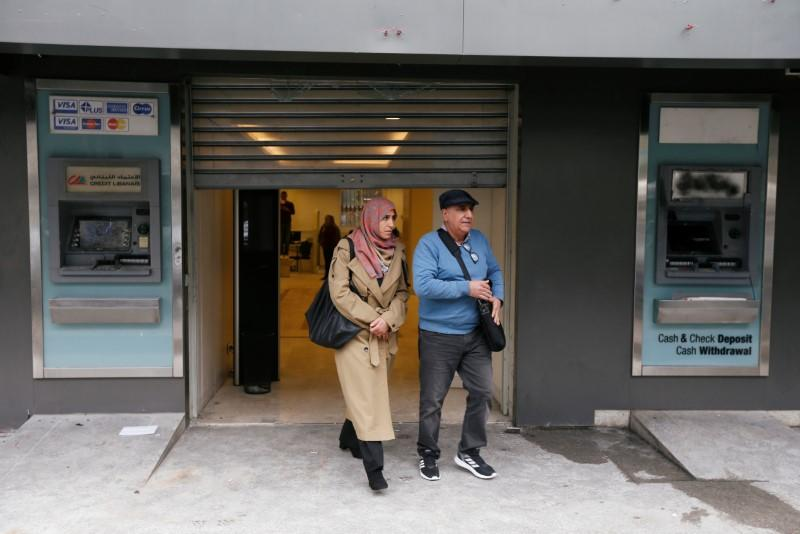 People walk past damaged ATM machines as they leave the Credit Libanais bank in Beirut