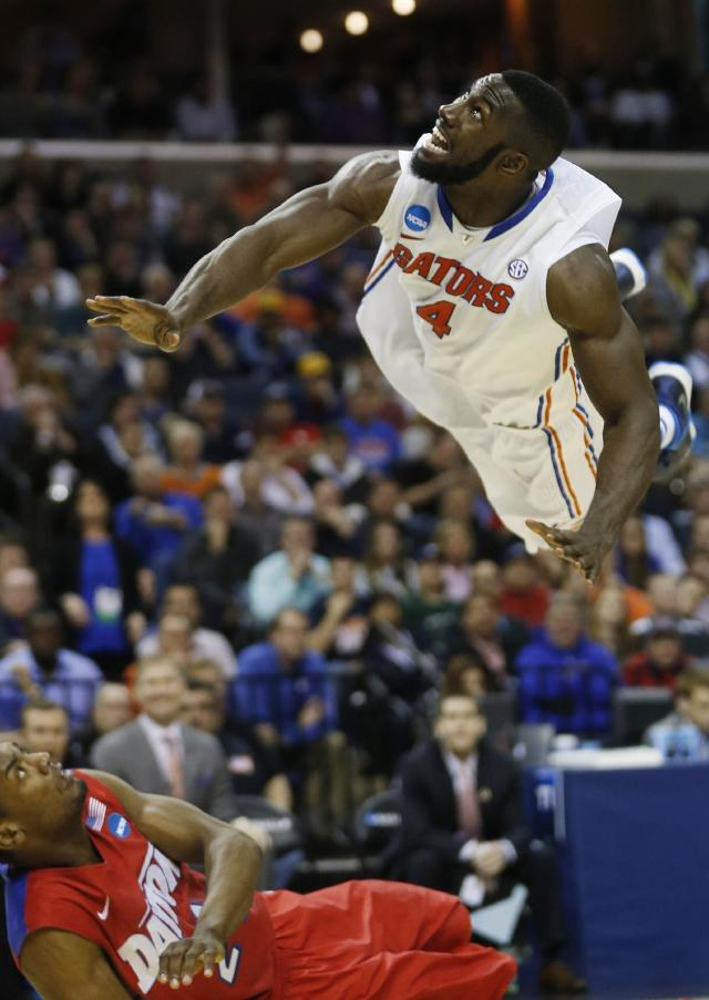 Florida center Patric Young (4) watches his shot as Dayton forward Dyshawn Pierre (21) falls to the floor during the second half in a regional final game at the NCAA college basketball tournament, Saturday, March 29, 2014, in Memphis, Tenn. (AP Photo/John Bazemore)
