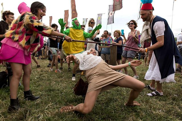 <p>Festival goers limbo at the Glastonbury music festival at Worthy Farm, in Somerset, England, Thursday, June 22, 2017. (Photo: Grant Pollard/Invision/AP) </p>