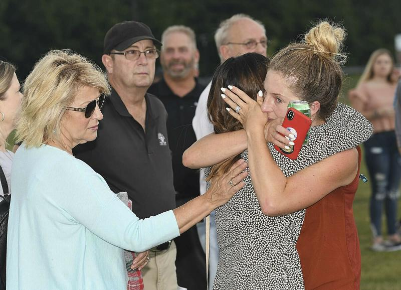 Aryn Fonda, right, hugs, Jade Oar,  who was friends with Delaney Wykle during a prayer vigil that was held for the victims of the helicopter accident Thursday, July 11, 2019  at the Paul Cline Memorial Sports Complex in Beckley, W.Va.  Chris Cline, his daughter Kameron Cline, Beckley native Delaney Wykle and four others were killed last week when their helicopter crashed after taking off from a remote private island in the Bahamas.  (Rick Barbero/The Register-Herald via AP)