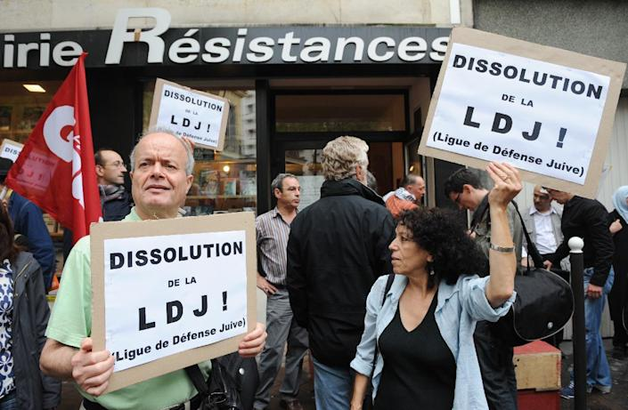 """People hold signs reading """"Dissolution of the LDJ! (Jewish Defense League)"""" during a demonstration in Paris on July 8, 2009 (AFP Photo/Boris Horvat)"""
