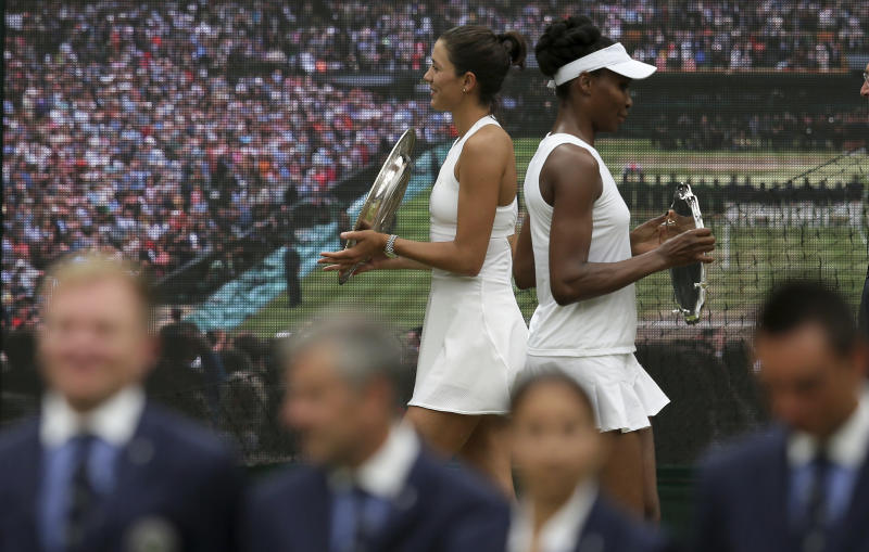Spain's Garbine Muguruza, left, holds the winners trophy after defeating Venus Williams of the United States, right, in the Women's Singles final match on day twelve at the Wimbledon Tennis Championships in London Saturday, July 15, 2017. (AP Photo/Tim Ireland)