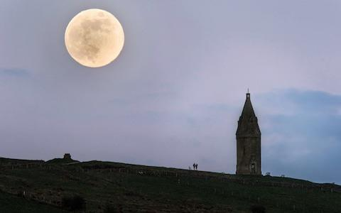 A couple watch the Pink Moon rise beside Hartshead Pike on April 29, 2018 in Manchester, England - Credit: Anthony Devlin