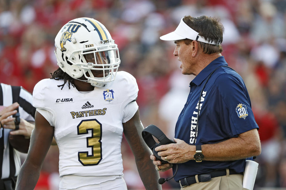 Florida International coach Butch Davis, right, talks to Richard Dames (3) during the first half of an NCAA college football game against Texas Tech, Saturday, Sept. 18, 2021, in Lubbock, Texas. (AP Photo/Brad Tollefson)