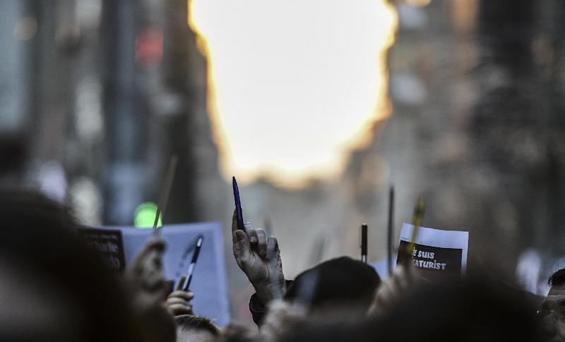Turkish journalists hold pencils and boards in front of the French consulate in Istanbul on January 11, 2015