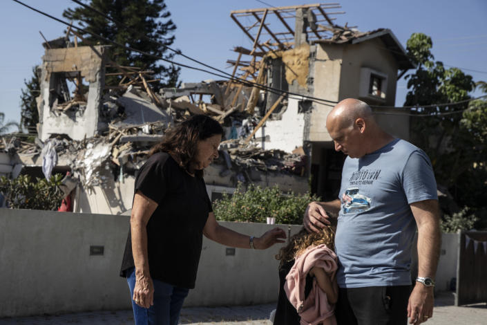 A young girl is comforted by her father next to a house damaged by a rocket fired from the Gaza Strip, in Yehod, central Israel, Wednesday, May 12, 2021. The house was hit on May 11, as barrage of rockets fired from the Gaza Strip toward central Israel. (AP Photo/Heidi Levine)