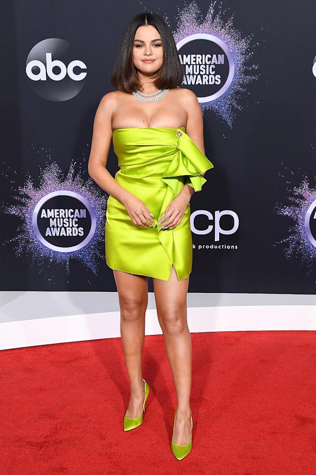 sports a strapless neon green Versace minidress with ruching, teamed with matching pumps and stacked Roberto Coin diamond necklaces.