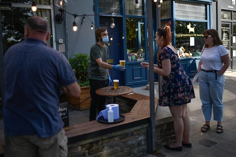 LONDON, ENGLAND - MAY 28: People are seen buying takeaway pints at a pub on Wandsworth Common on May 28 2020 in London, England. The prime minister announced the general contours of a phased exit from the current lockdown, adopted nearly two months ago in an effort curb the spread of Covid-19. (Photo by Peter Summers/Getty Images)