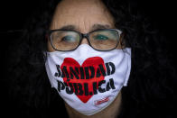 """A demonstrators attends a protest to demand more resources for public health system in Madrid, Spain, Sunday, Nov. 29, 2020. The organizers delivered a manifesto to the Madrid regional authorities demanding the end privatization of the health system. The face mask reads in Spanish """"Public health system"""". (AP Photo/Bernat Armangue)"""