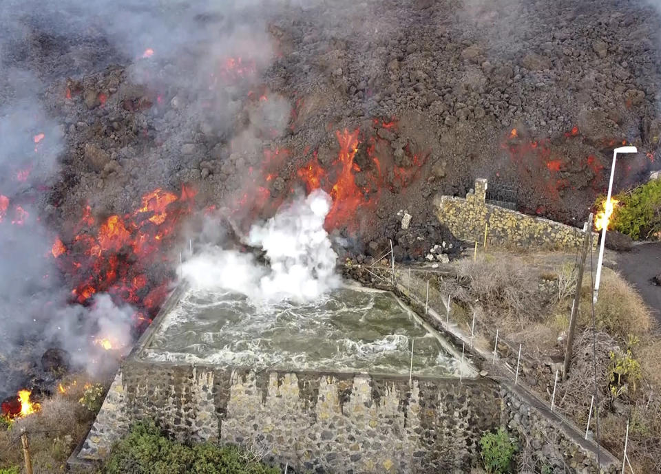 Hot lava reaches a balsa normally used for for irrigation after an eruption of a volcano on the island of La Palma in the Canaries, Spain, Monday Sept. 20, 2021. Giant rivers of lava are tumbling slowly but relentlessly toward the sea after a volcano erupted on a Spanish island off northwest Africa. The lava is destroying everything in its path but prompt evacuations helped avoid casualties after Sunday's eruption. (Europa Press via AP)