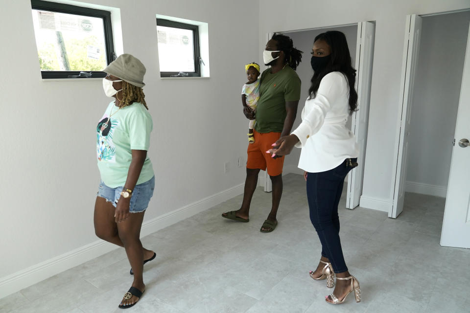 Realtor Keva Chester, right, walks with first time home buyers Fatima Heath, left, and Willie Hardemon, center, as they do a walk through at the Twin Homes, Sunday, April 18, 2021, in the Overtown neighborhood of Miami. (AP Photo/Lynne Sladky)