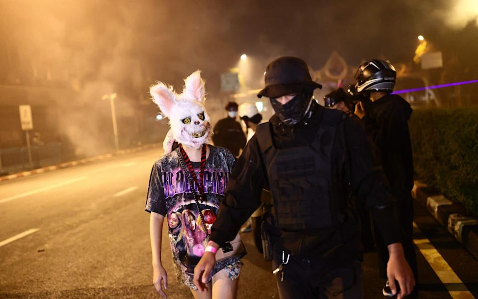 Anti-government protesters, one wearing an animal head as another wears protective gear, walk together after police fire tear gas during a demonstration to mark the 15-year anniversary since the 2006 military takeover in Bangkok on 19 September 2021, as they urge the resignation of the current administration over its handling of the Covid-19 pandemic - Jack Taylor/AFP