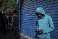 "A man looks down as he holds his lottery ticket on a street in the capital Addis Ababa, Ethiopia Friday, Nov. 13, 2020. Tensions over the deadly conflict in Ethiopia are spreading well beyond its cut-off northern Tigray region, as the federal government said some 150 suspected ""operatives"" accused of seeking to ""strike fear and terror"" throughout the country had been detained. (AP Photo/Mulugeta Ayene)"