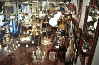 In this Nov. 22, 2013 photo, rare chandeliers and light fixtures are among the large inventory of unique antiques at the Olde Good Things store in New York. The store's Christian missionary owners offer their well-heeled customers a heart-warming story: Part of the proceeds pay for the group's orphanage in Haiti, one of the poorest countries in the world. What they don't say is that even though they claim in IRS filings to be spending around $2.5 million annually, the home for boys and girls was so dirty and overcrowded during recent inspections that the government said it shouldn't remain open. (AP Photo/Bebeto Matthews)