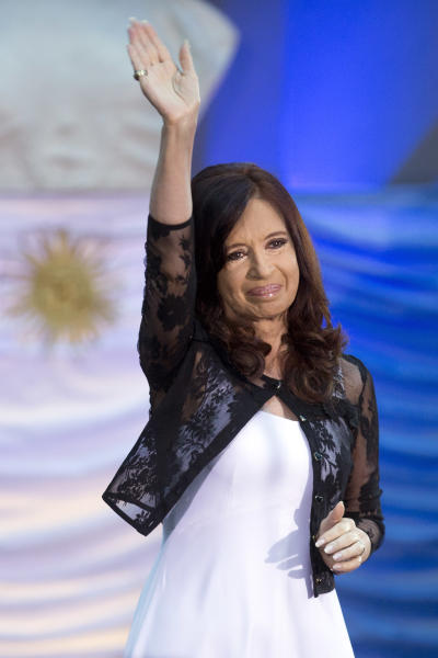FILE - In this Dec. 10, 2013 file photo, Argentina's President Cristina Fernandez waves at a celebration marking the 30-year anniversary of democracy's return in Buenos Aires, Argentina. Fernandez has tried to reinvent her image since her return from skull surgery. She's put aside the all-black wardrobe she wore for three years mourning her late husband Nestor Kirchner, and reshuffled her Cabinet. (AP Photo/Victor R. Caivano, File)
