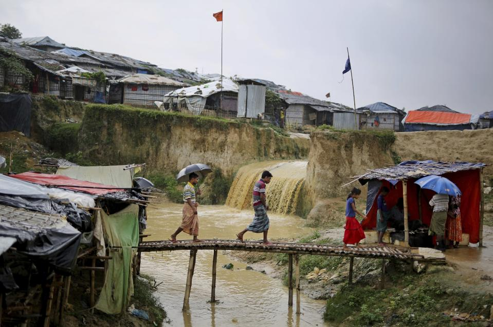 FILE - In this Aug. 28, 2018, file photo, sewer water flows in the back as Rohingya refugees cross a makeshift bamboo bridge at Kutupalong refugee camp, Bangladesh. A fire in a sprawling Rohingya refugee camp in Bangladesh Thursday, Jan. 14, 2021, has destroyed hundreds of homes. (AP Photo/Altaf Qadri, File)