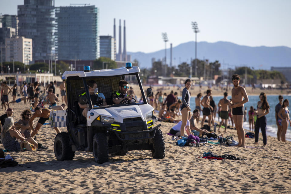 Police officers patrol the beach in Barcelona, Spain, on Wednesday, May 27, 2020. Roughly half of the population, including residents in the biggest cities of Madrid and Barcelona, are entering phase 1, which allows social gatherings in limited numbers, restaurant and bar service with outdoor sitting and some cultural and sports activities. (AP Photo/Emilio Morenatti)