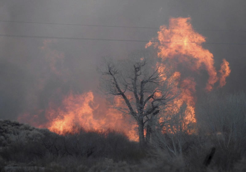This Sunday, Feb. 18, 2018 photo taken by the Bishop California Highway Patrol and released by the Inyo County Sheriff's Office shows smoke rising from wildfires near Bishop, Calif. A wind-driven wildfire in rural central California forced mandatory evacuations and threatened hundreds of buildings Monday, including a historic railroad station, after it tripled in size overnight, officials said. (Bishop California Highway Patrol via AP)