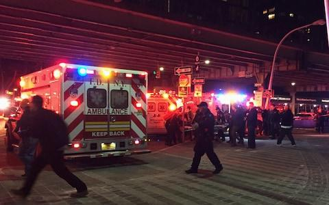 First responders carry a person to an ambulance after the crash in the East River - Credit: AP