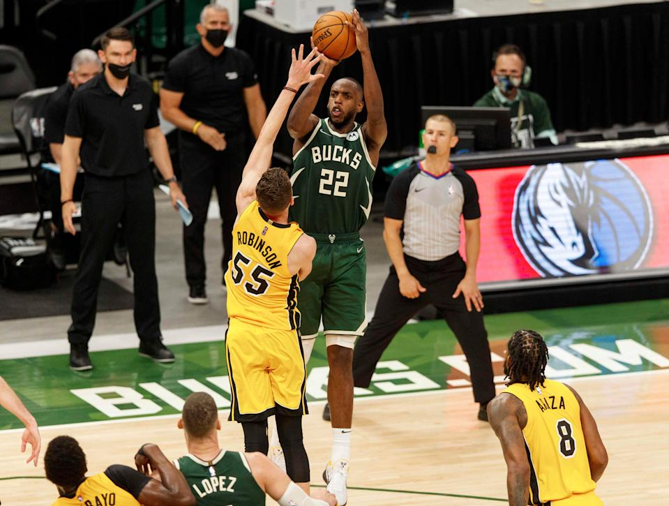 Milwaukee Bucks forward Khris Middleton makes the game-winning basket over Miami Heat forward Duncan Robinson with less than a second to go in overtime.